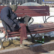 The homeless sleeps on a bench in city square — Stock Photo