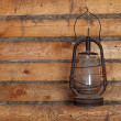 Stock Photo: The old kerosene lamp hanging on the wall of a wooden house