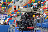 Fragment of stadium about many rows of multi-colored chairs and camera — Stock Photo