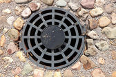 A round grille sewage wells to drain rain and melt water — Stock Photo