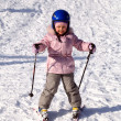 A happy little girl off skiing with slides - Stock Photo