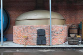 Ochakovo brewery museum, street composition, the old brew kettle with a flame heating — Stock Photo