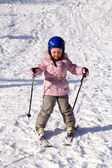 A happy little girl off skiing with slides — Stock Photo
