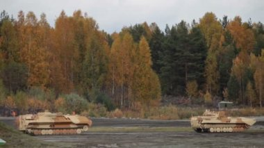 Heavy armoured military vehicles rides on the field along the forest — Stock Video