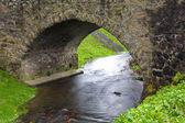 Old stone bridge over a small river in spring time — Stock Photo