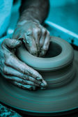 Hands working on pottery wheel ,  artistic  toned — Stock fotografie