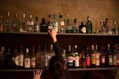Waitress and bar shelves full of alcoholic beverages bottles — Stock Photo