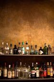Bar shelves full of alcoholic beverages bottles — Stock Photo