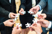 Teamwork - Business people solving a puzzle — Stock Photo