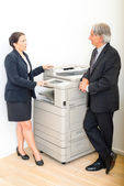 Colleagues talking at copying machine in the office — Stock Photo