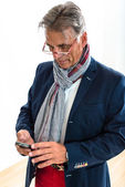 Stylish pensioner checking his mobile phone — Stock Photo