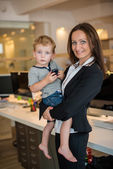 Businesswoman with small child in the office — Stock Photo
