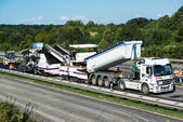 Tipper unloading fresh asphalt from body into tracked paver during pavements construction works — Stock Photo