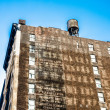 Old urban building with list of former brands in new york — Stock Photo