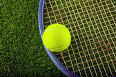 Tennis ball and racket over grass — Stock Photo