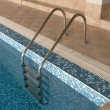 Ladder in swimming pool - Stock Photo