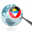 Magnified flag of antigua and barbuda with blue globe - Stock Photo