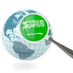 Magnified flag of saudi arabia with blue globe — Stock Photo
