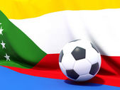 Flag of comoros with football in front of it — Stockfoto