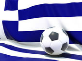 Flag of greece with football in front of it — Stockfoto