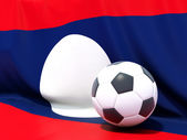 Flag of laos with football in front of it — Stok fotoğraf