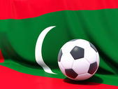 Flag of maldives with football in front of it — Stok fotoğraf