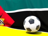 Flag of mozambique with football in front of it — Stok fotoğraf