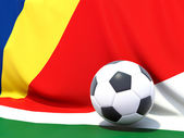 Flag of seychelles with football in front of it — Stock fotografie