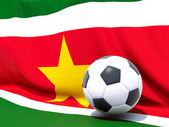Flag of suriname with football in front of it — Stok fotoğraf
