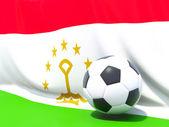 Bandera de tayikistán con fútbol delante de ella — Foto de Stock