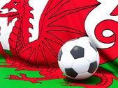 Flag of wales with football in front of it — Stok fotoğraf