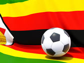 Flag of zimbabwe with football in front of it — Stok fotoğraf