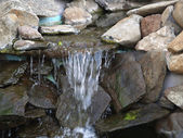 Manmade rock waterfall fountain pond outdoors moss — Stock Photo