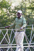 Afro american man standing on suspension bridge — Stock Photo