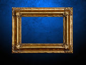 Picture frame on blue grungy wall — Stock Photo
