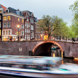 Canal Bridge and Boat Tour in Amsterdam at Evening — Stock Photo #26831475