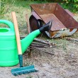 Tools for work in a garden is a watering-can and wheelbarrow — Stock Photo