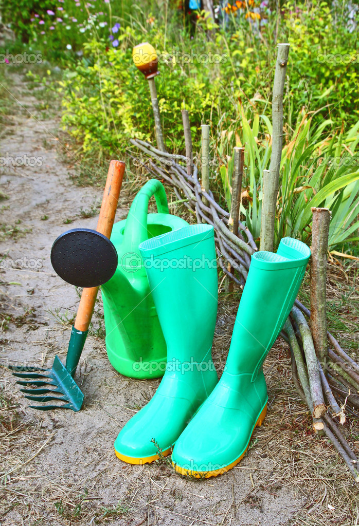 Green garden watering-can, rubber knee-boots and rakes — Stock Photo #12186352