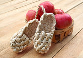 Rural still life with apples and sandals made of bark — Stock Photo