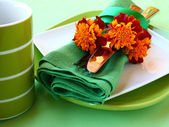 Decorative dreen serviettes with flatwares and marigolds — Stock Photo