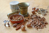 Copper mortar and nuts on a wooden table — Stock Photo