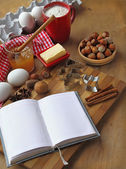 Opened recipesbook and ingredients for cookies — Stock Photo