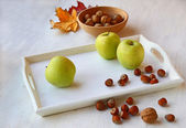 Apples and nuts on a white tray — Stock Photo