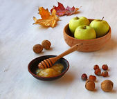 Apples, honey and nuts on a white table — Stock Photo