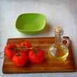 Empty bowl for lettuce and  tomatoes next to the bottle of olive — Foto de Stock