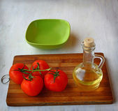 Empty bowl for lettuce and tomatoes next to the bottle of olive — Stock Photo