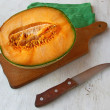 Half of pumpkin with a knife on table — Stock Photo