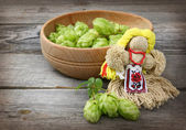 Doll motanka of thread and a bowl of freshly harvested hops — Stock Photo