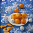 Plate with mandarin oranges and Christmas knitted angel — Stock Photo