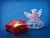 Candlestick and angel on a blue background. — Stock Photo